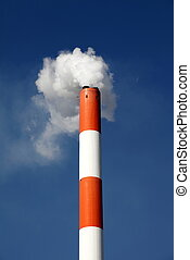 Smokestack with pollution against a blue sky