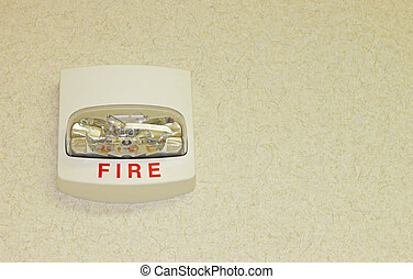 A Fire alarm on a textured wall with room for your text