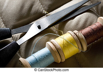 Thread bobbins with scissors on a gray fabric