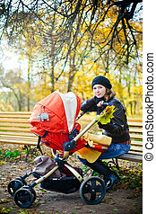 Motherhood And Autumn - young beautiful happy mother sitting...