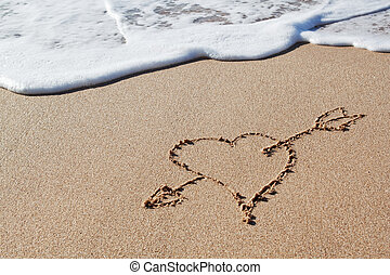 Cupids arrow to the heart in the sand