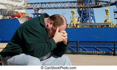 Depressed Man At Shipyard - Depressed unemployed man sits on...