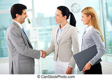 Partnership - Portrait of successful associates handshaking...