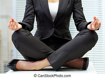 Yoga on table - Close-up of female in suit sitting on...
