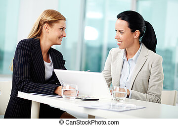 Working together - Portrait of two young women at workplace...