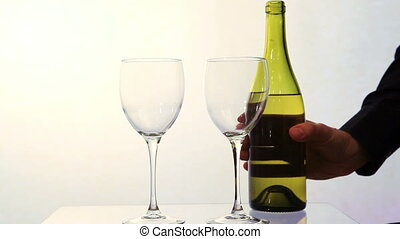 White wine poured from bottle into two glasses