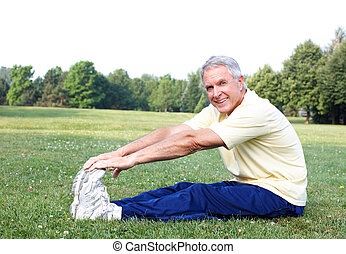 Senior man doing yoga - Senior man doing yoga in the park