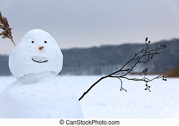 Snowman Waving its Twig Arm in Greeting before a Frozen Lake...