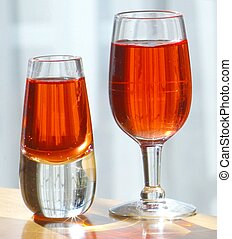 TWO LIQUEUR GLASSES - Two cordial glasses containing amber...
