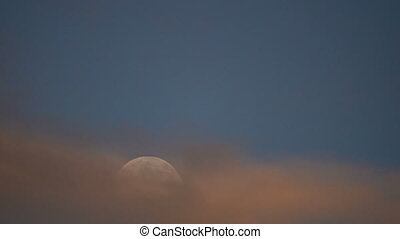 Moon rising through clouds - Time lapse clip of a full moon...