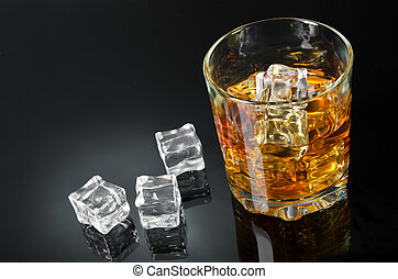 Whisky with ice - Glass of whisky with ice on a black...