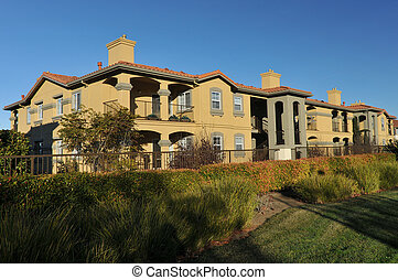 Condo on a walking path with grass - A three story...