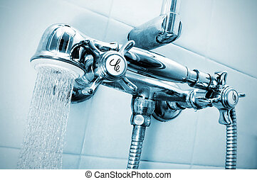 take a shower - closeup of the faucets of a shower with a...
