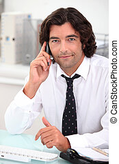 Handsome office worker making a phone call