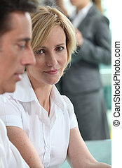 Focus on a woman sitting with colleagues