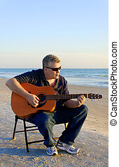 Guitar by the Sea - A middle-aged man playing at guitar at...