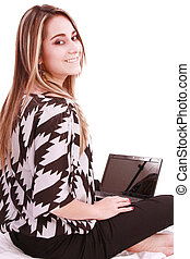 Portrait of beautiful woman using laptop while looking at...