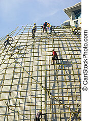 Closeup of construction worker assembling scaffold on...