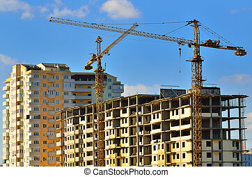 Tower cranes on building of the many-storeyed house