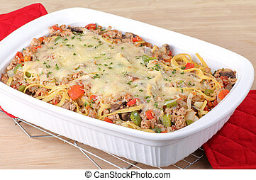 Casserole Dish - Noodle casserole with melted cheese in a...