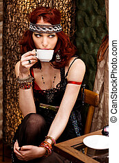woman in retro clothes drinks coffee in cafe bar