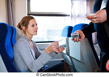 Young woman traveling by train, having her ticket checked by...