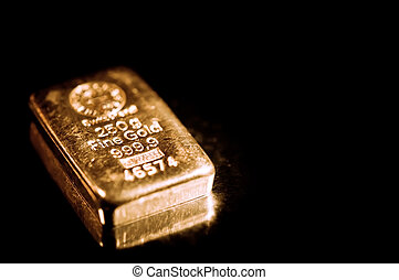 fine gold ingot isolated on a black background shallow depth...