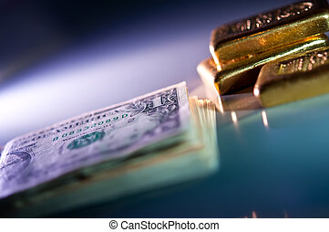 gold and money - stack of banknotes and gold bars on blue...