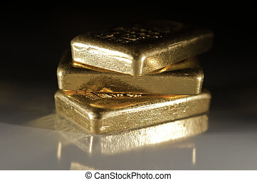 Gold Ingots - three gold ingots on a dark grey background...
