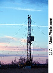 Drilling rig. - Vertical view of a drilling rig on a sunset...