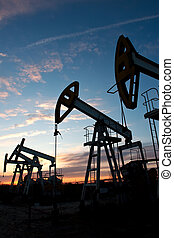 pump-jack - oil pumps on the sunset sky background