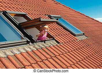 The window - The little girl in the roof window .