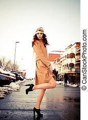 winter fashion - young woman wearing coat walking down the...
