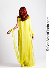 stylish - red hair woman in long elegant stylish yellow...
