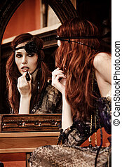 reflexion - elegant woman applying lipstick in front of...