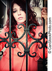 woman behind fence - red hair woman in pink coat behind...