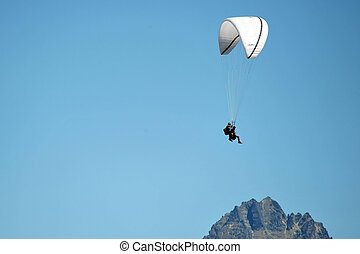 Man Parachuting - Two men tandem skydive with blue sky in...