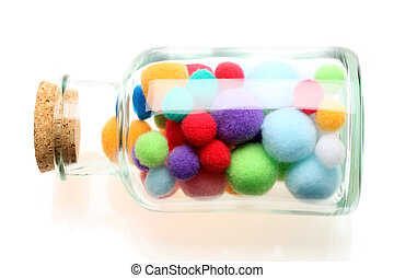cotton balls - Colorful cotton balls in a bottle on white