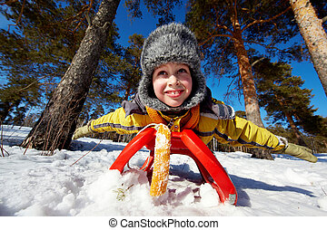 Boy on sledge - Cute boy in winterwear lying on sledge in...