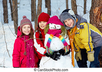 Friendship - Happy friends in winterwear with snowman...
