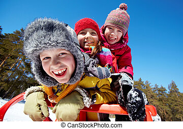 Winter happiness - Happy friends in winterwear tobogganing...