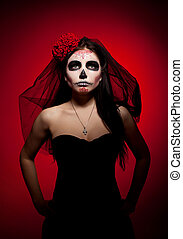 Serious woman in day of the dead mask on red - Young woman...