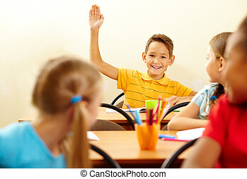 Boy raising arm - Image of smart pupil raising arm during...