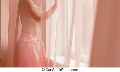belly dancing at the window - woman dancing belly dance at...