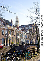 Dutch canal with old houses, church and bridge with blue sky