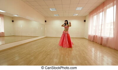 Bellydance - woman perform a belly dance in dancing school