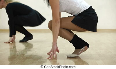 dance studio - woman with personal coach stretching in dance...