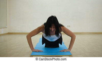 woman doing push-ups in a fitness center
