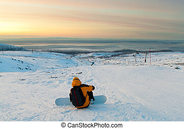 Snowboarder sitting on the slope