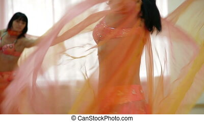 Belly dance performance in front of a mirror in the dance...
